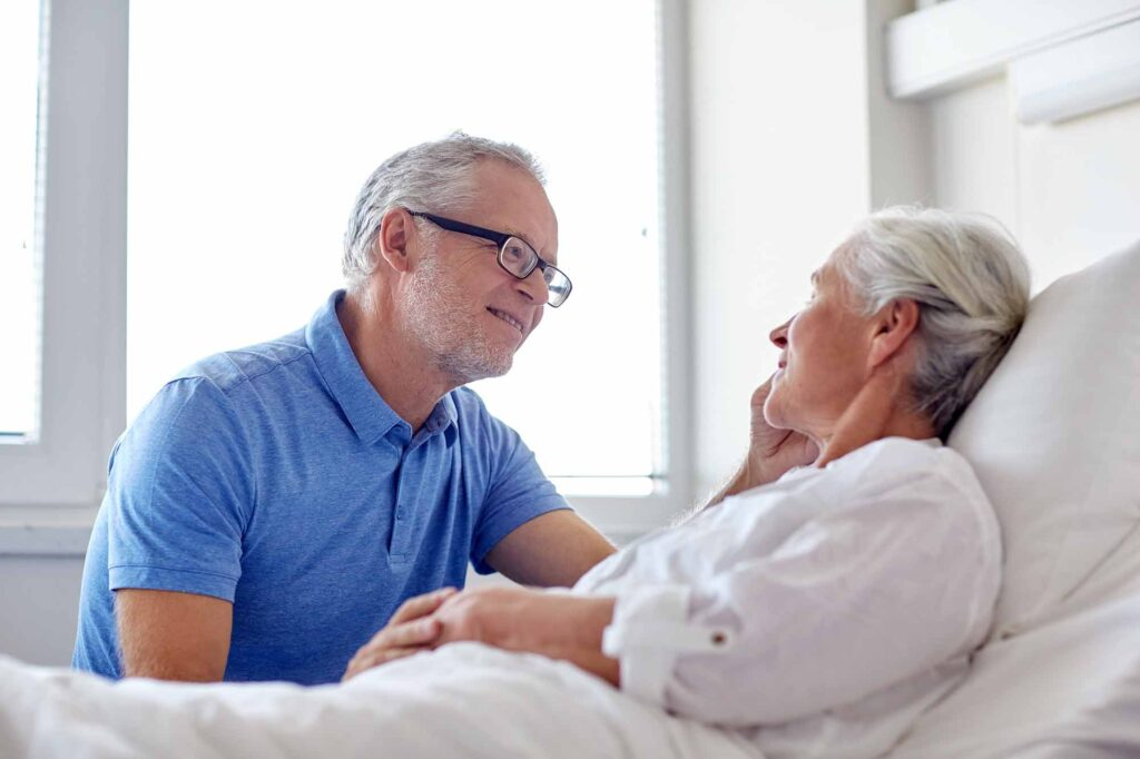 mature man next to hospital bed of elderly woman